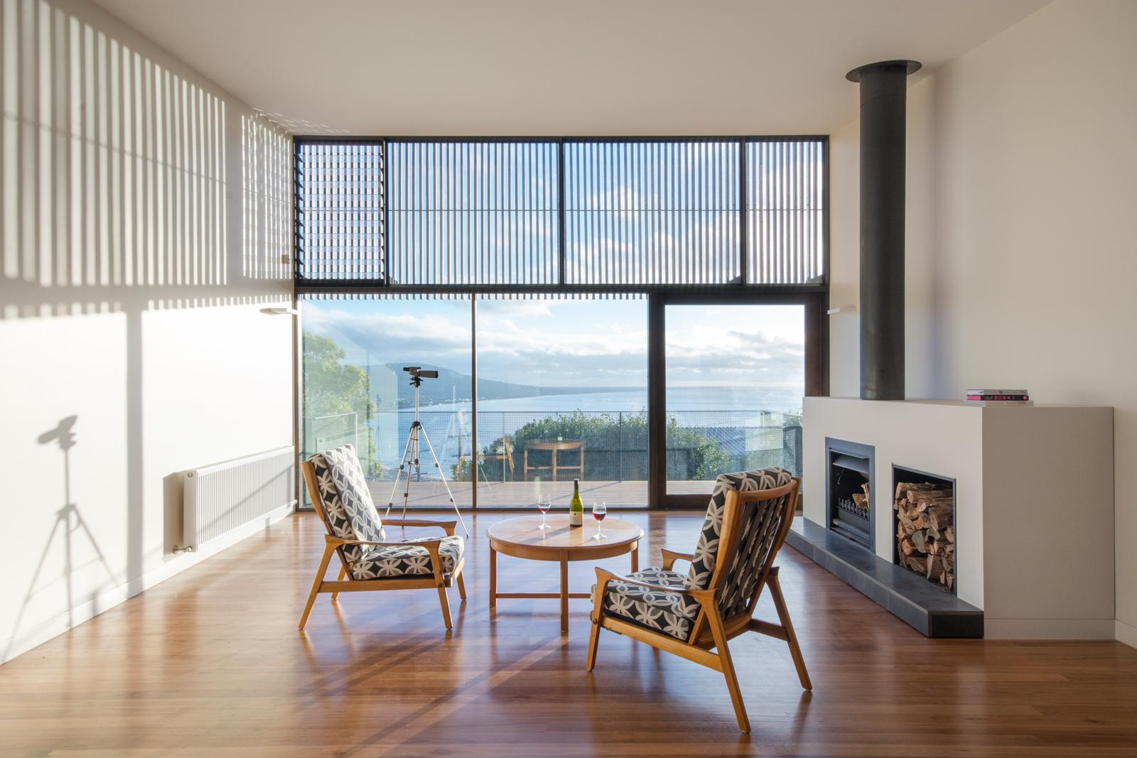 Living room with ocean views in Australian beach home by OLA Studio