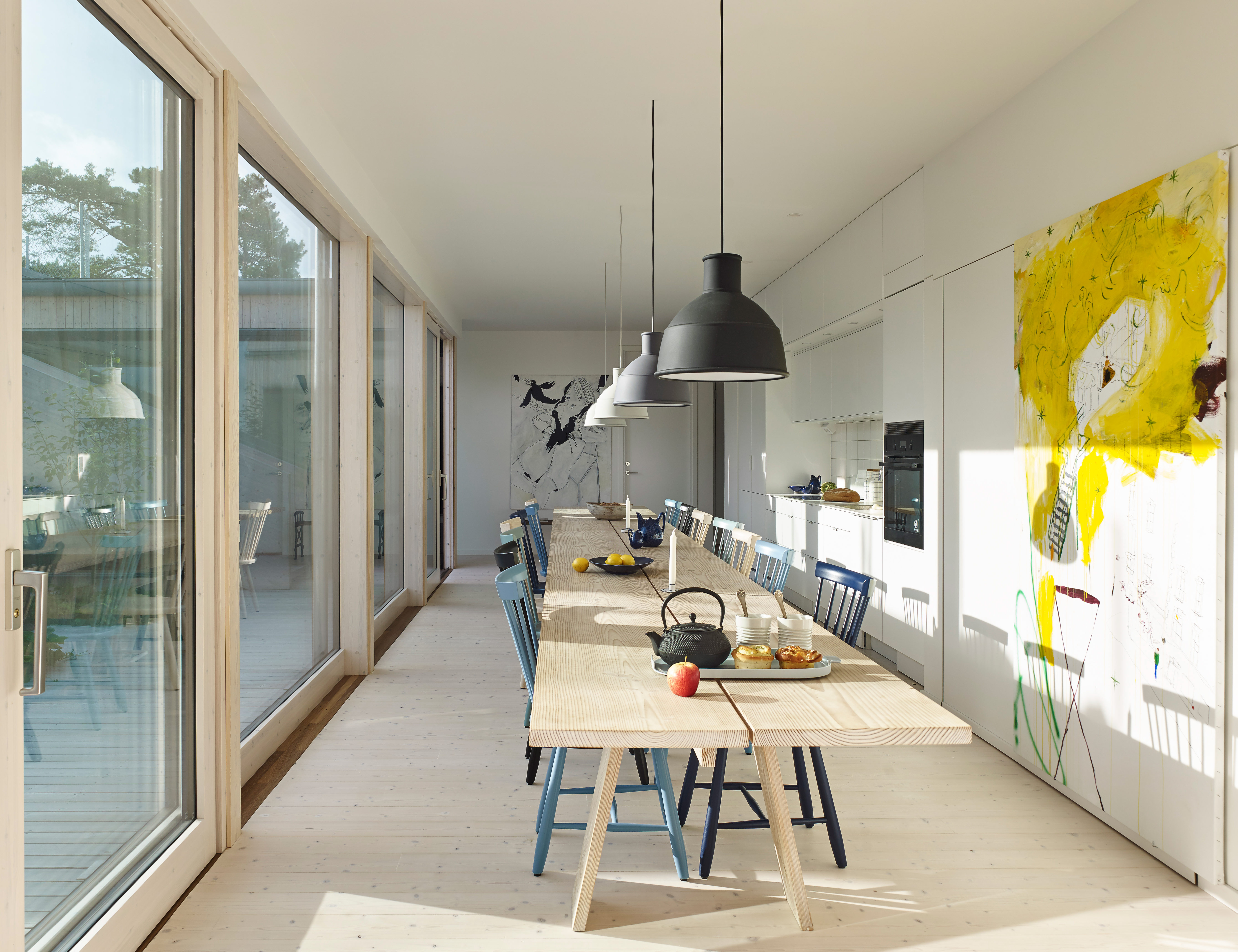 A custom table designed by Staffan Holm sits under Unfold pendants by Form Us With Love for Muuto and features Lilla Åland chairs by Carl Malmsten for Stolab