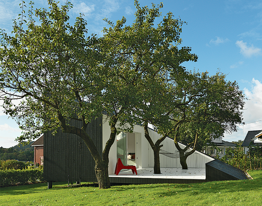 modern guesthouse in norway with angular facade and cutaway patio with spruce cladding and ikea chair