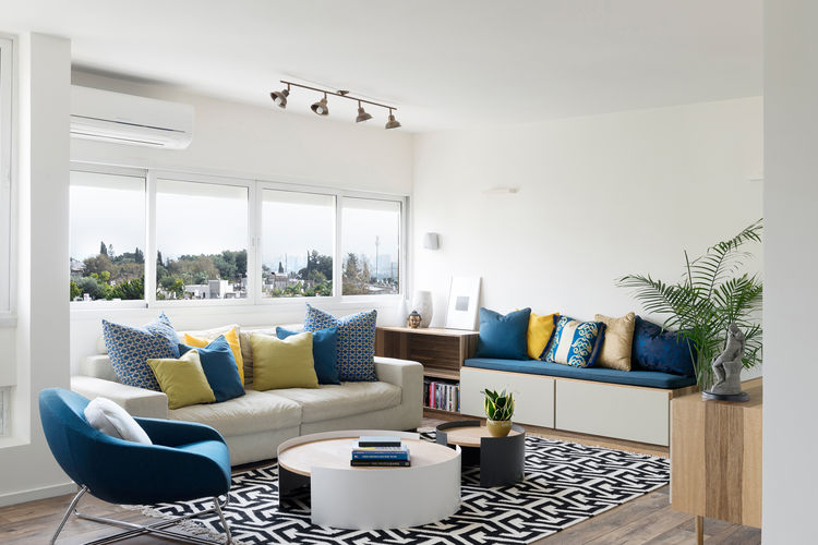 A minimal living room with yellow and blue pillows.