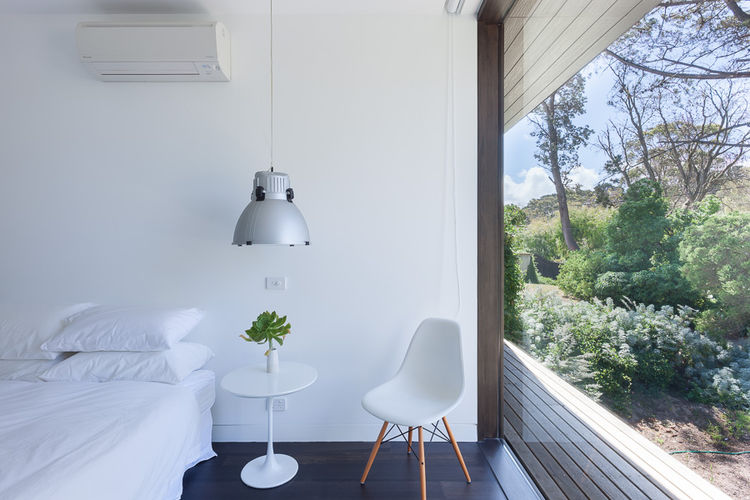 An Il Guzzini pendant light and Eames chair in a bedroom