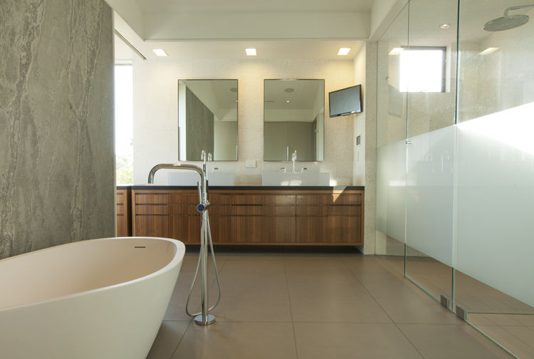 The master bathroom of a beach house with a bathtub by Porcelanosa.