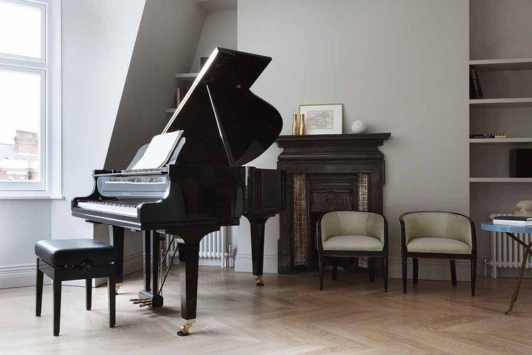 An original fireplace and mini grand piano at a London renovation