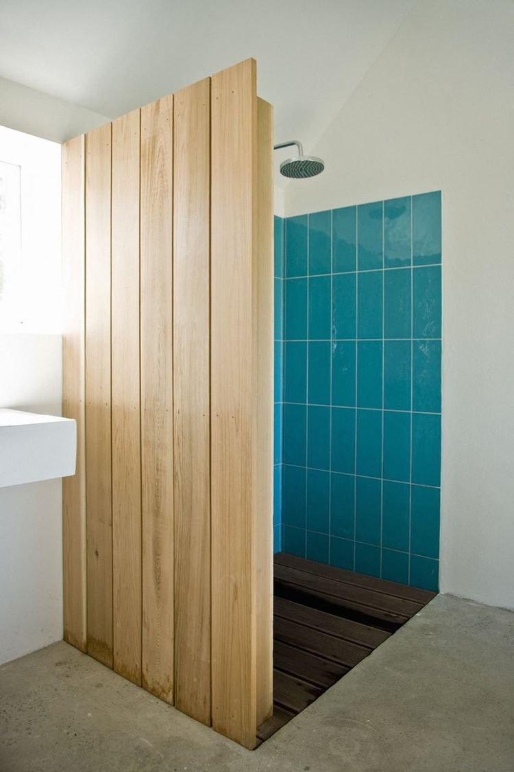 "Colored tiles in the shower are revealed behind a cedar wood wall. ""The sound of falling water on wood and the surrounding fields form the background,"" say the architects. ""This was our way of introducing an immaterial idea of what luxury actually could b"