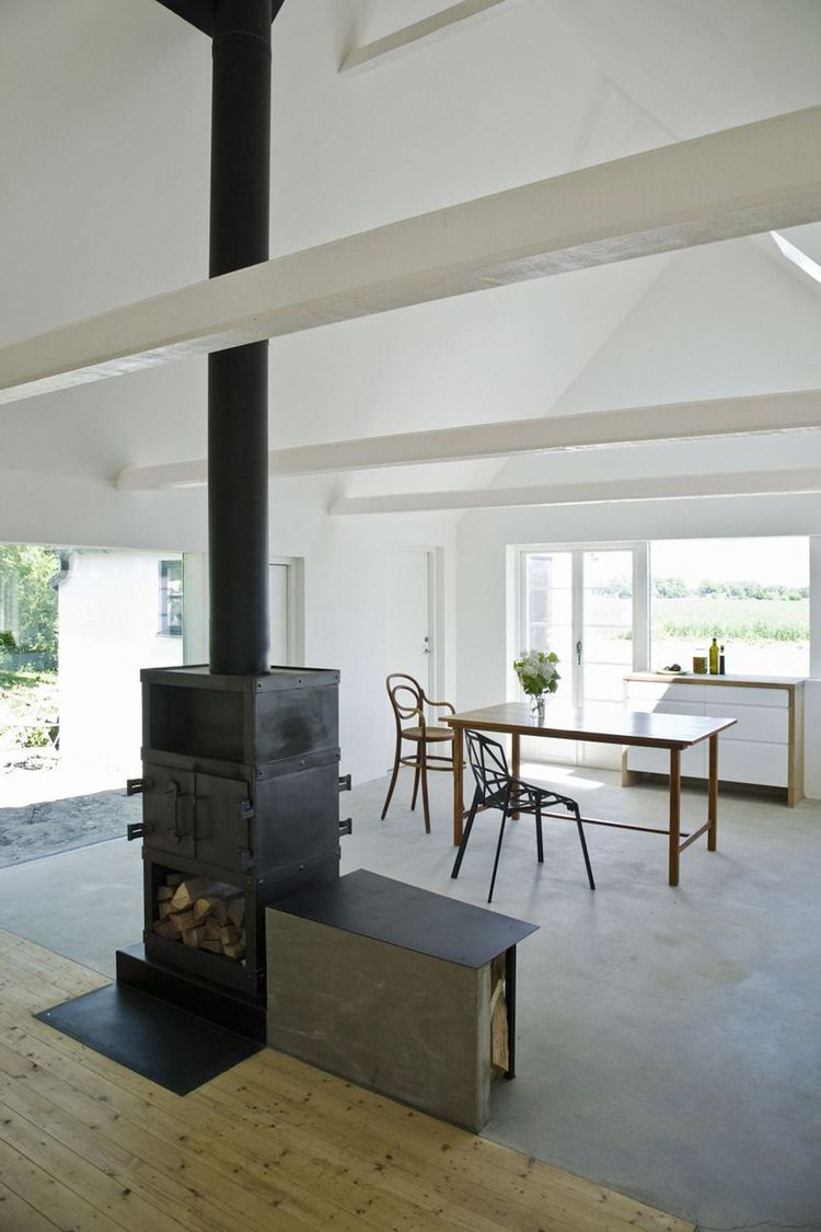 The two-­sided stove is installed in the heart of the house, elevated slightly to bring the fire closer to eye-­level. The stove marks the meeting of the new concrete floor with the old wooden floor. Photo by Laura Stamer.