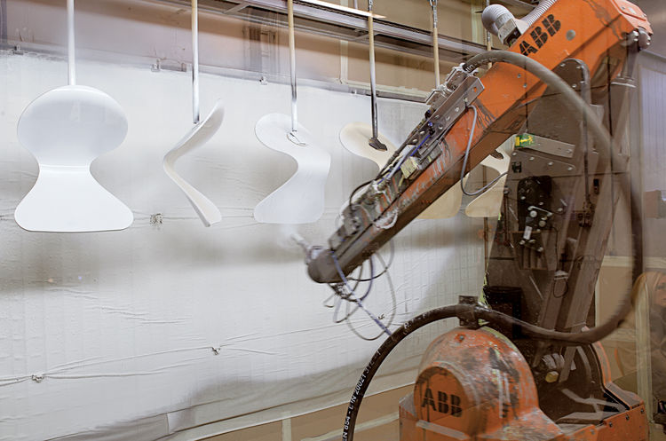 A robotic arm paints the hanging chairs for optimum coverage.