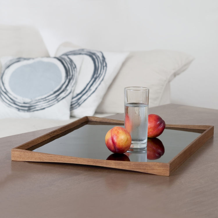 Architect Finn Juhl designed predominantly in the 1940s and 50s and created the TurningTray in 1956 to match the furniture in his house. The curvature of the teak eliminates the need for handles and the two sides—one laminated in black and the other in ei