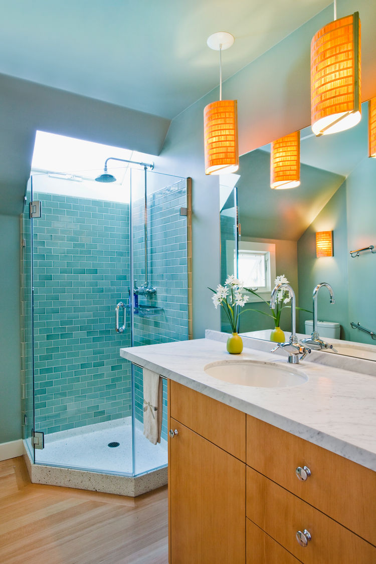 The upstairs bathroom was fitted with a skylight over the shower, adding light and spaciousness to the small room. Locally made Heath tiles line the new shower, and a marble slab salvaged from wainscot at Brooks Brothers in San Francisco now serves as the