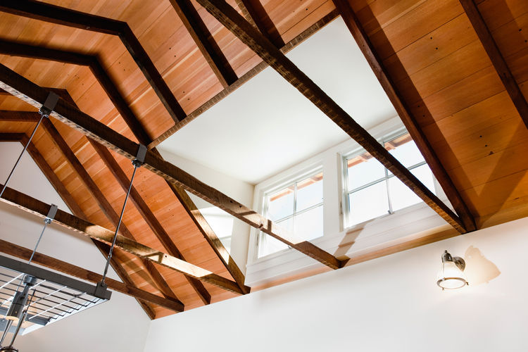 The original rafters in the kitchen are exposed and topped with salvaged fir bleacher seating. The high ceilings allow the warmer air to stratify near the ceiling. A south-facing clerestory brings light deep into the space.
