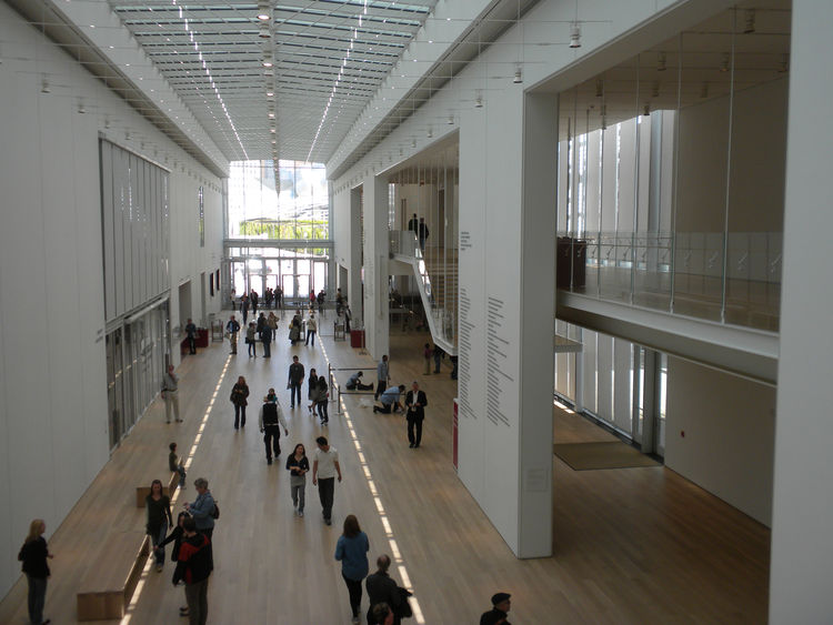 """Looking down the Modern Wing on the second floor, you can see hints of Millennium Park through the northern wall of glass. Above is Piano's """"flying carpet"""" roof that was designed to let natural light into the gallery spaces without causing damage to the p"""