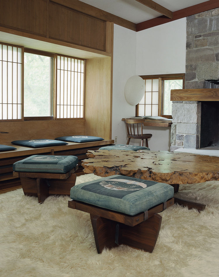 The living room in Nakashima's Reception House features several Greenrock ottomans and a Buckeye burl coffee table. The complex also includes a pool, arched pool house, workshop barn, and studio, among other structures.