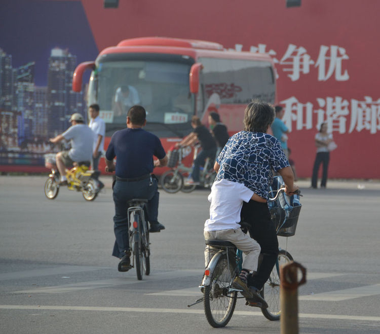 At an intersection in Langfang, Shahid spotted this child hiding his head on the back of a bike.