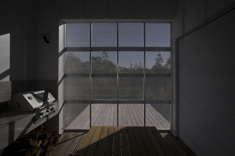 A sliding screen shelters the barbecue deck while still allowing light in.