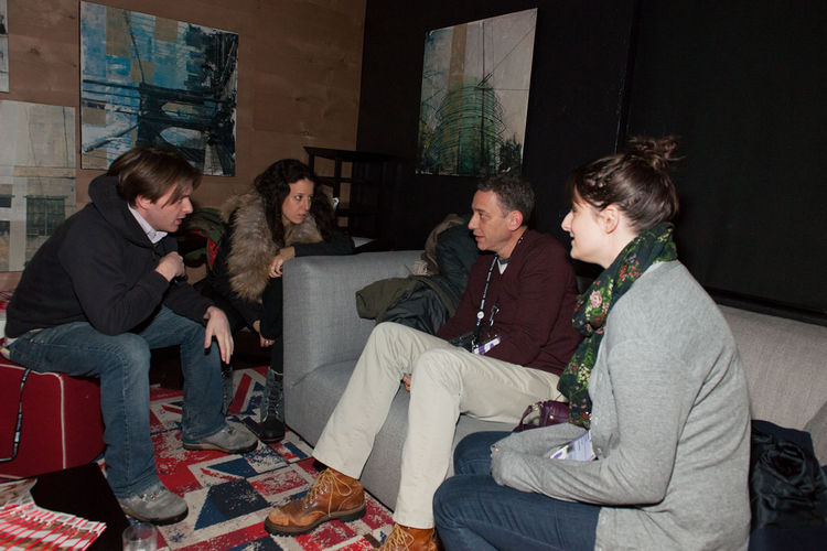 More partygoers recline on a Soho sofa from Poliform, with the Anglophilic Hey Jack tile from FLOR underfoot.