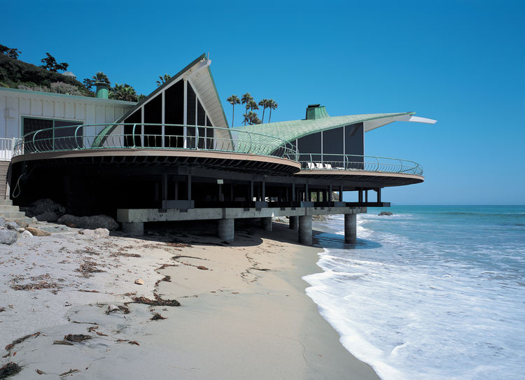 White paint now covers the exterior walls of the Cooper Wave house, and the beach has shrunk over the decades since the house was built (1957–59), which has forced the current owners to construct new supports in the form of massive concrete caissons now v