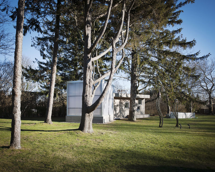 """The art studio makes a clear delineation of """"his"""" space and """"her"""" space. His, wrapped in translucent polycarbonate, draws in the light and meshes inside and out. Hers, clad in cedar, is a more private box, as the programming flip-flopped several times dur"""