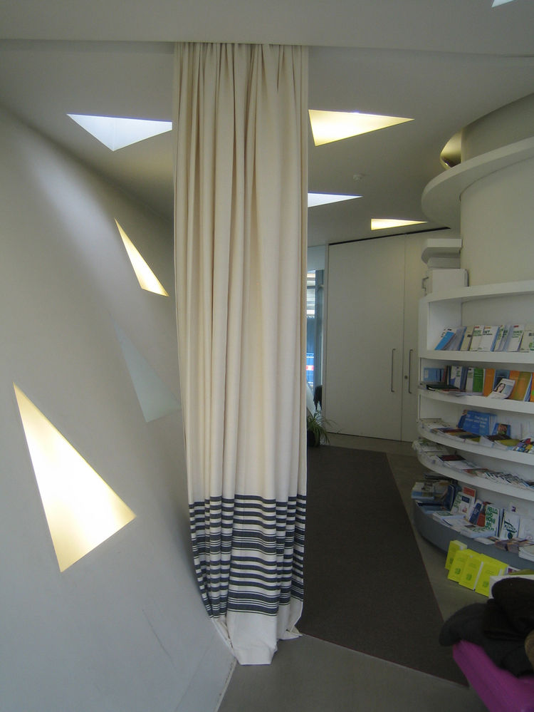 One of Hadid's design goals was to make the space as flexible as possible, so though there are two private rooms where people can meet behind closed doors, the main social spaces are defined by a pair of curtains which themselves can offer some privacy wi