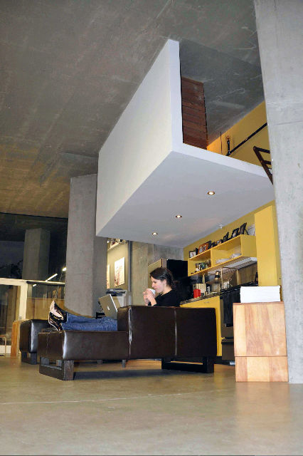 "Colkitt hung the sleeping loft from the concrete ceiling using five steel rods—often used to support heavy mechanical equipment—hidden in the wall. The rods, each of which can hold 1,000 pounds, allow for the loft's open, almost floating, construction. ""I"
