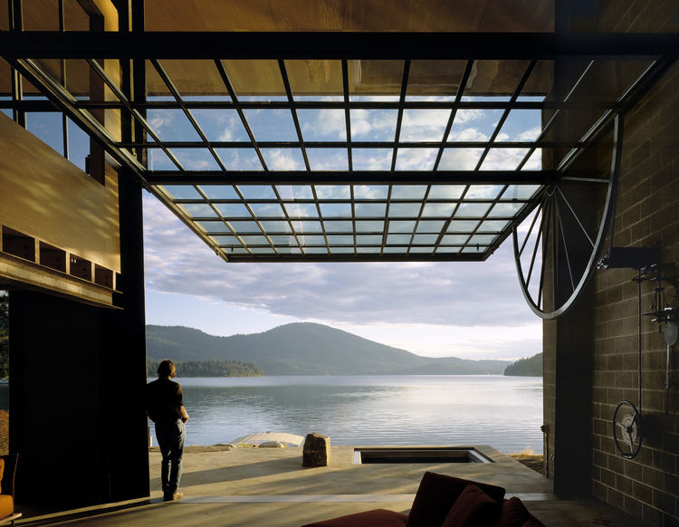 "In Hayden, Idaho, the <a href=""http://www.olsonkundigarchitects.com/About/Leadership/TomKundig"">Tom Kundig</a>-designed Chicken Point Cabin sits on the edge of a quiet lake. The 20-by-30-foot, glass wall transforms into a door and can be completely opened"