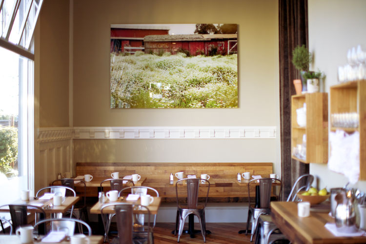 "At the end of the dining room, an image by Kelli Yon hangs above the counter. ""She's a local artist we like who traveled around this spring to photograph local farms,"" Bleskacek says. ""We tried to find something with a plow but we loved this beautiful pic"