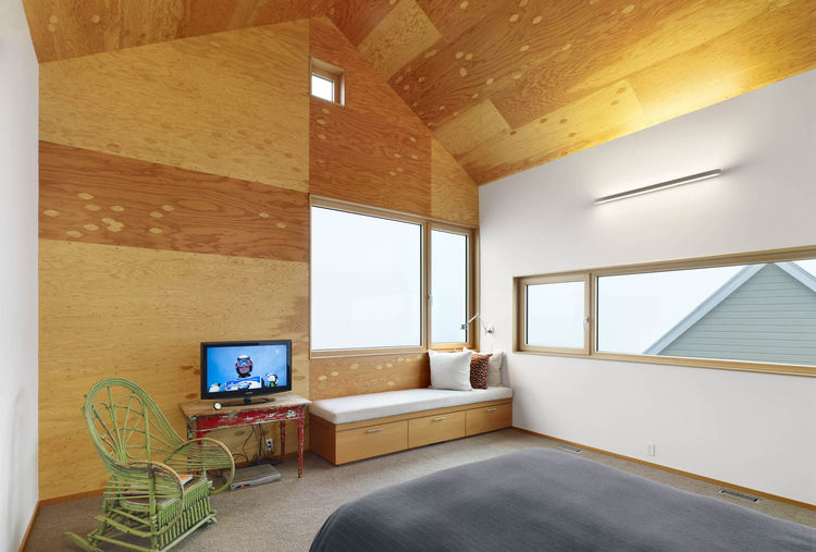 Inside the master bedroom, the juxtaposition of old and new is pronounced. Wooden furniture sits next to a streamlined built-in bench. The wood-framed windows open up to views of the gabled roof.