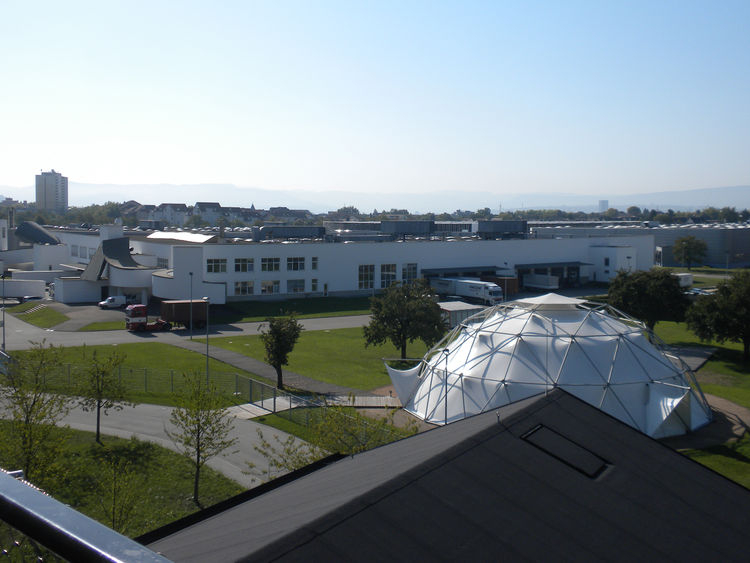 "The ends of the longhouse structures feature large glass windows and the very top one opens onto a balcony that overlooks the Vitra campus. The white dome was designed by <a href=""http://www.dwell.com/people/buckmister-fuller.html"">Buckminster Fuller</a>"
