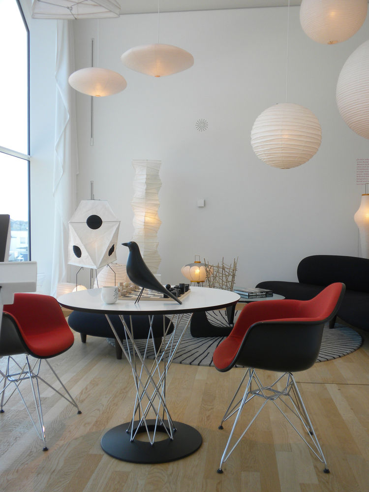 "This living room setting is devoted to <a href=""http://www.dwell.com/people/isamu-noguchi.html"">Isamu Noguchi</a>, with a hit of Eames in the DAR Eames Plastic Armchairs and Eames House Bird atop the Noguchi Dining Table. In the background are the Freefor"
