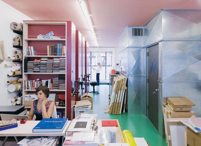 The studio space includes room for the full-time archivist to work. Note the library-style storage along the wall, with shelves that crank along a track.
