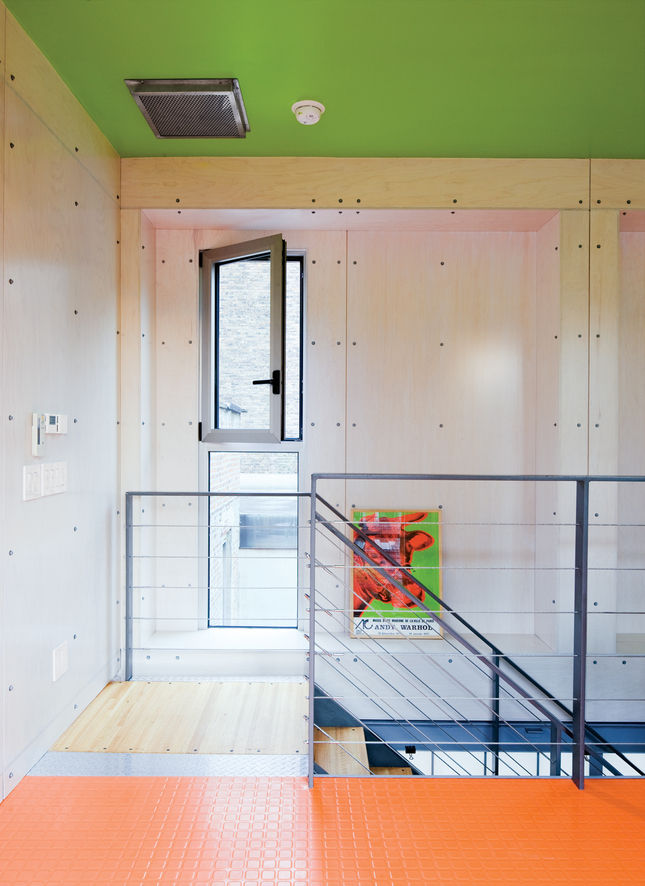 The house has many unexpected splashes of color, and exposed industrial materials are used throughout. The diamond-plate steel shown here was also used as a kitchen backsplash, covered with a coating of pink paint.