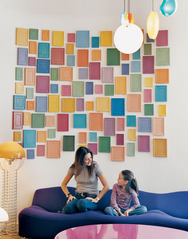 Cleménce and daughter Clara hang out on a Pierre Paulin sofa, under an installation by artist Alan McCollum.