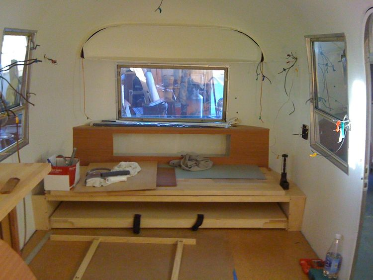 Brandes and Area 63 Productions designed this custom built-in platform sofa bed for the back of the Airstream. The lower platform pulls out and swings up on special hinges to turn the sofa into a queen size bed.