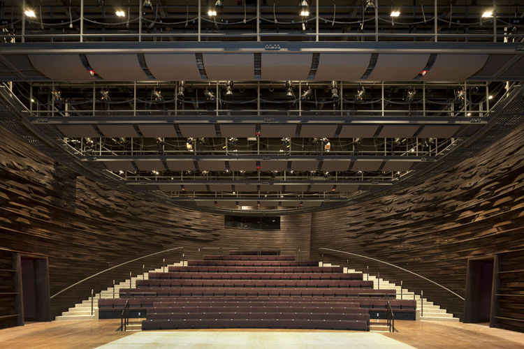 """""""The outside is concrete and the inside is wood, like an oyster with a rough exterior,"""" Thom says of the Kogod. The rippling wall is composed of 3/8th-inch-thick poplar in a basket-weave pattern. """"This allows the sound to scatter, and gives the place char"""