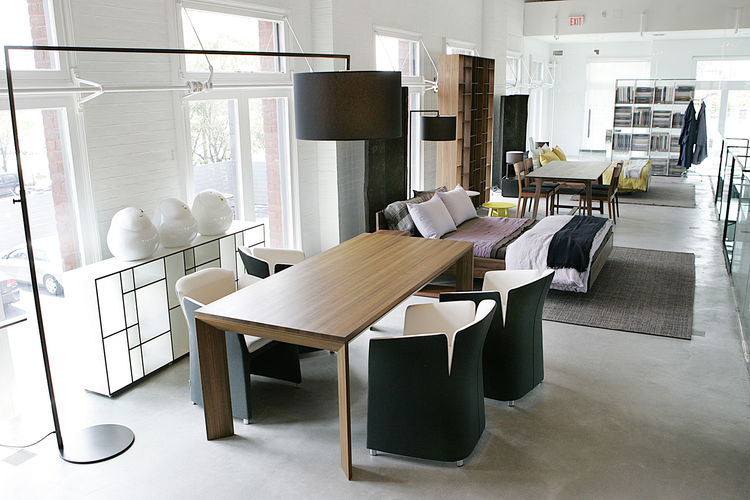 In one of the showroom's many intriguing display combinations, four of Simon Pengelly's 2008 Lotus dining chairs are matched with a beveled-leg table from Mutscher Winkler Design. The 2006 High Noon floor lamp is by Germany's El Schmid.