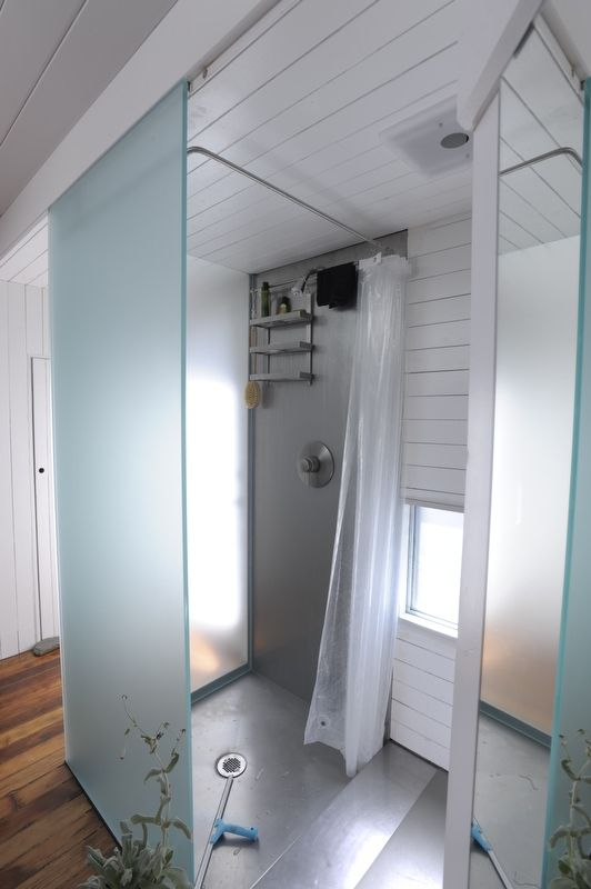 "With two sides made of etched glass, the shower enclosure is ""a cool green lantern when lit from within,"" says Azevedo. The recessed stainless steel shower pan is a custom design made by a Bay Area fabrication shop that's no longer in business. Photo by S"