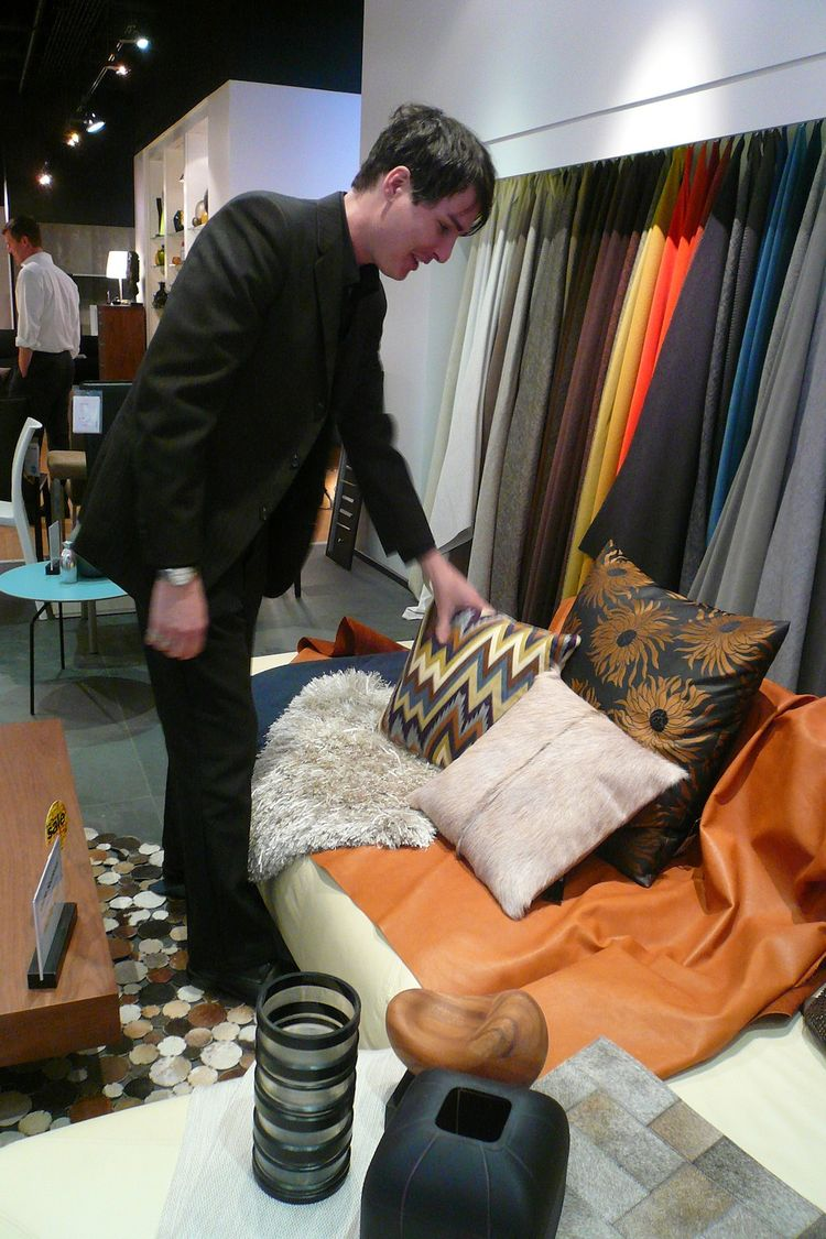 Here's Christopher laying out the fabrics for the pricier option... I'm smitten with the buttery camel-colored leather. The cowhide, shiny shag rug, and upholstered pillows less so.