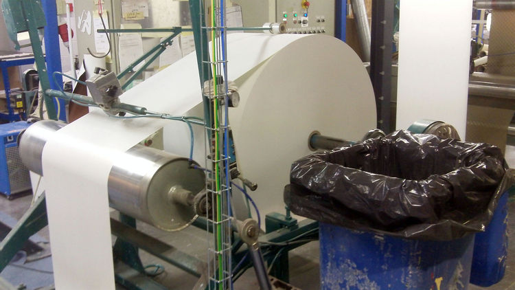 Vast, 300-meter-long rolls are threaded into the machine to begin the printing process by applying a solid base coat.