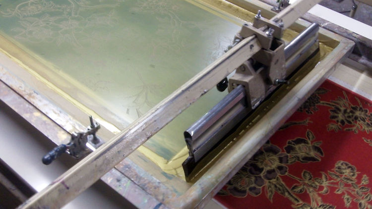 During screenprinting, ink is applied over a gauze-y screen patterned with very fine holes and then forced through the screen with a wide squeegee-like device that is pulled across its surface.