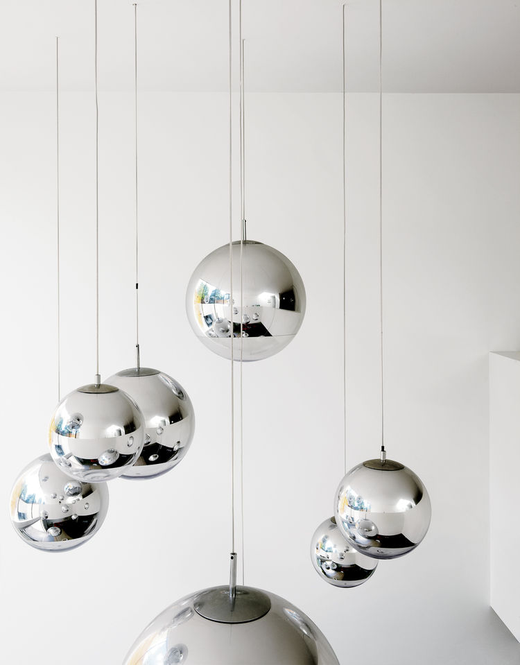 """Bruce worried about what to put in the double-height space above the kitchen table—–until he found these Tom Dixon–designed mirror balls. """"They were installed at random and when William came over that evening, he said, 'Fantastic, well done.' So we left t"""