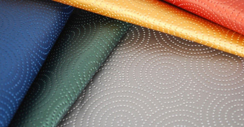 "Kravet's <a href=""http://www.kfi.net/mkting/kravet/stakleen_long.html"">Sta-Kleen</a> performance fabric is a throwback to the 1950s formaldehyde resin fabrics, with its faux leather feel, raised circular designs and availability in five bright hues."