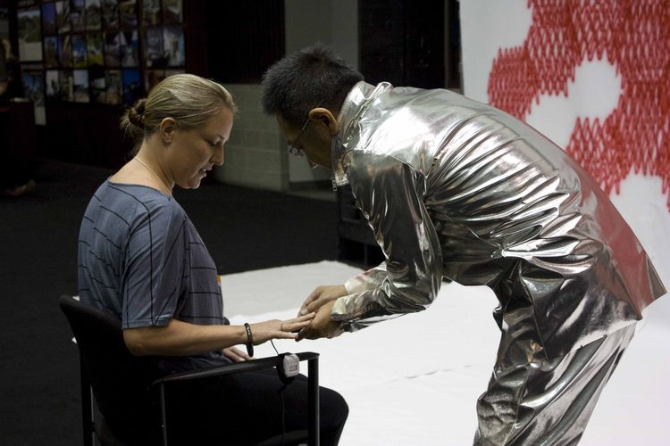 In a nutshell, Sasaki's booth was part performance piece, part charitable donation, and part painting. Sasaki, who was suited up in some mighty silvery duds, connected brave souls to a heartbeat monitor. Then, to the reverberating sound of the person's he
