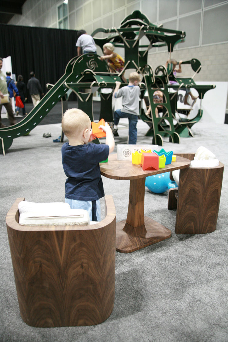 "While enrolled at FIDM, Heather Gallagher was paired with <a href=""http://www.pivotfurniture.com/"">Pivot Furniture</a> to produce a design for a class, and she came up with the Bloom Table playset, in striking organic European walnut with a hand-laid vene"