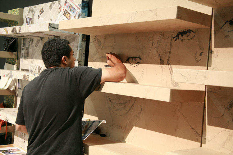 "In the <a href=""http://www.environmentfurniture.com/"">Environment</a> booth, artists worked through the weekend adding their creative touch to unfinished bookshelves."