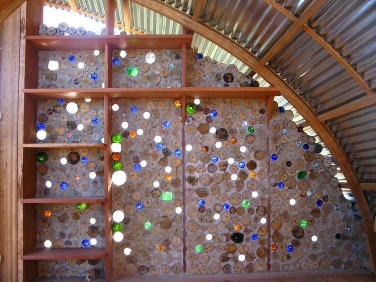 Nonn and Martin collected bottles from the roadside for use in the walls. The bottles let colored light filter into the cabana, and passing breezes create sound effects on the mouths of the bottles.