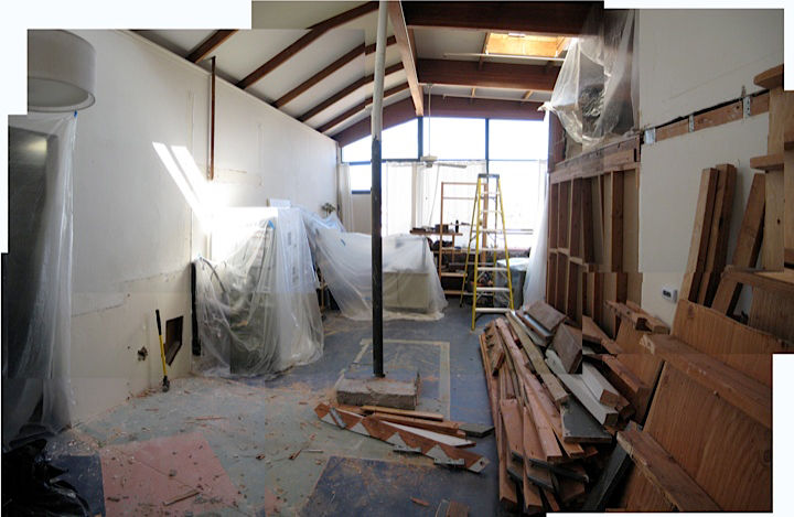 This shows the space opened up, breathing again, with all of the loft demolition down. You can see all the tarps—we would bunch all our furniture together and tarp everything off, tarp up the loft where our clothes were, and tarp of the passage to the kit