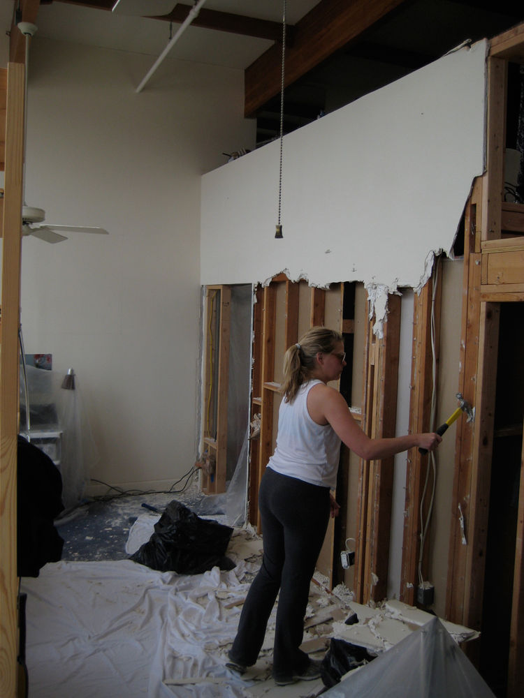 One of the few days I got Lynda to help with demolition! Here she is  removing drywall from the wall separating living room from bedroom.
