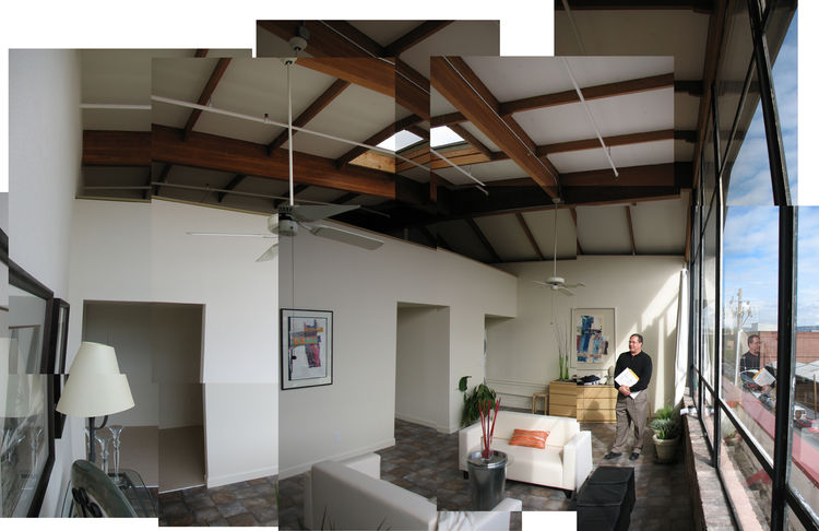 All of the furniture here was staged, and this is what we saw when we first visited the loft. The previous owners put down a cheap vinyl mat flooring that just laid on top of the floor; it wasn't even adhered. In the kitchen, they spread joint compound on
