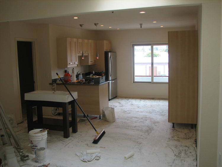 This is the kitchen flooring with the mat pulled up. Another reason we opted against the concrete grinding were these asphalt flooring tiles that were adhered to the original concrete. The previous owners spread this white leveling compound all over the f