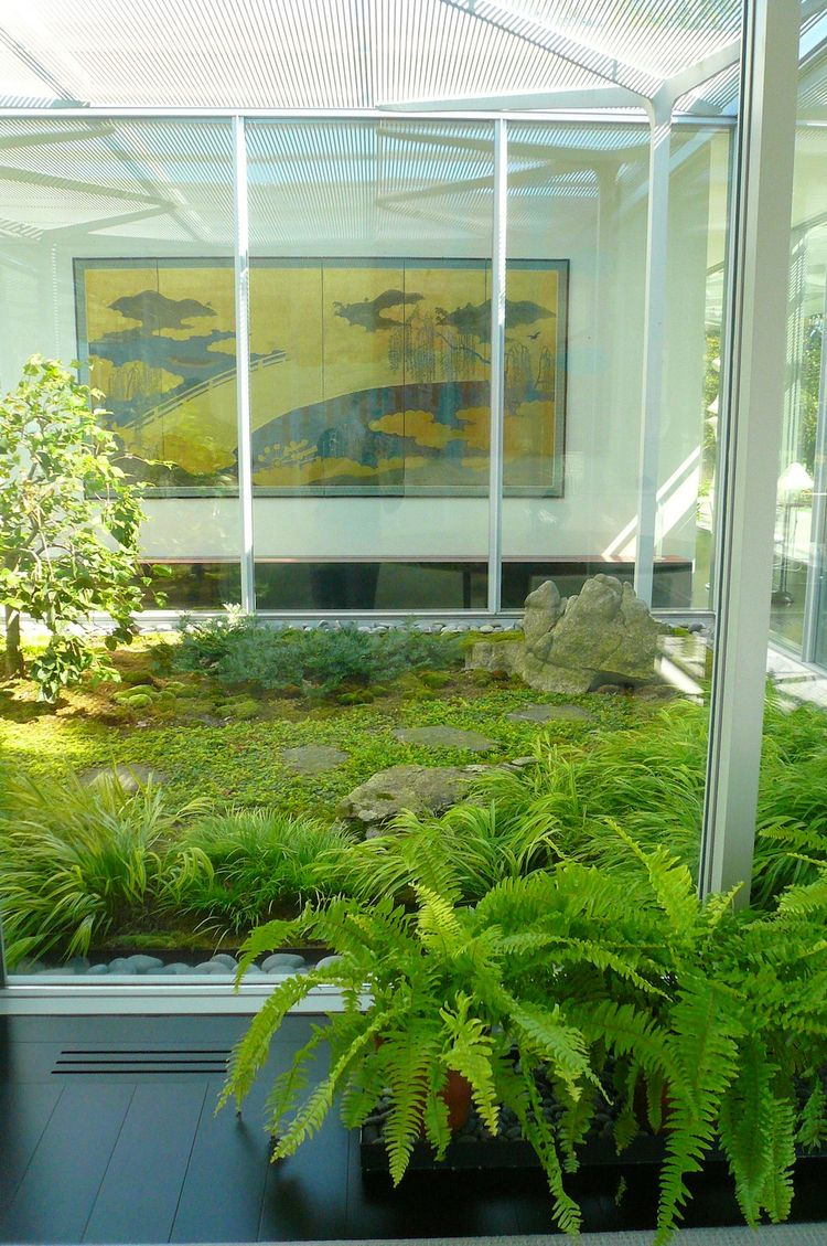 "Armstrong designed this mossy, zen courtyard garden to mark the division between the public area of the house (the loft-like living room) and his ""private inner sanctum"": the master bedroom and his-and-her bathrooms. The plantings pick up on the golden hu"