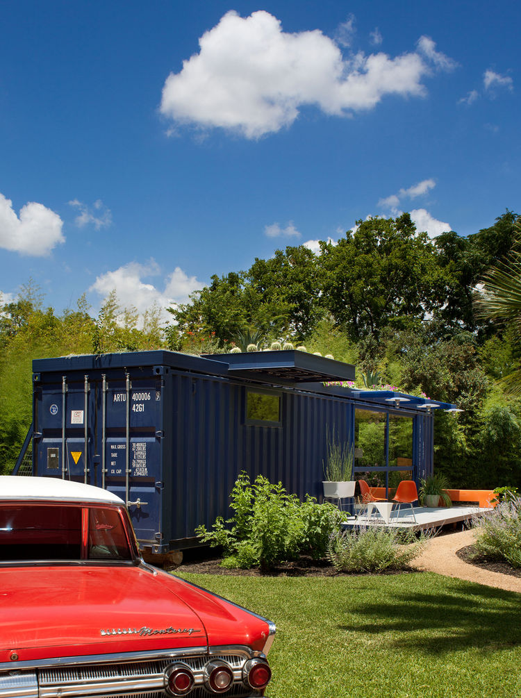 Hill's 1962 orange Mercury Monterey complements the blue of the container, whose original opening was retained on one end as the entrance to the garden storage shed.