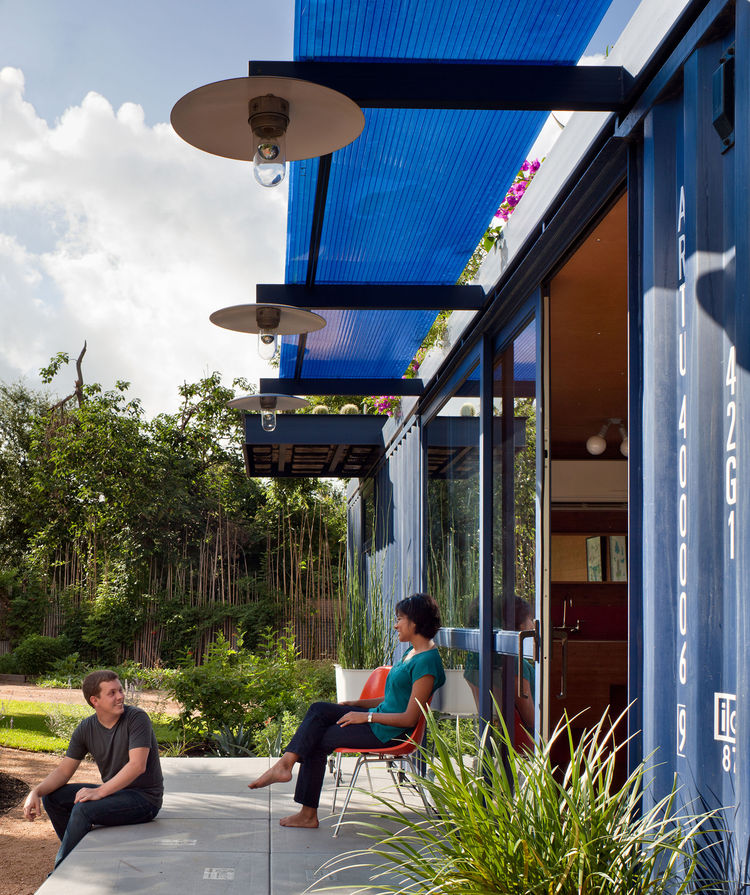 Friends of both the resident and the architect post up on the porch. Poteet attached beams to the container and topped them with a Polygal sheet for shade. The lamps were custom made by the architect from recycled tractor parts fitted with vapor lamps.